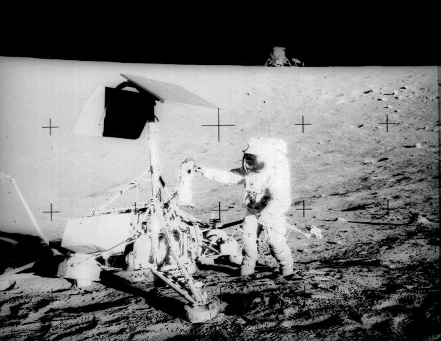 Pete Conrad standing at Surveyor 3, with the Lunar Module in the background
